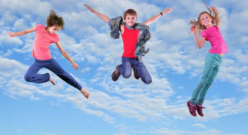 Gelukkige kinderen die en in de blauwe hemel uitoefenen springen stock afbeeldingen