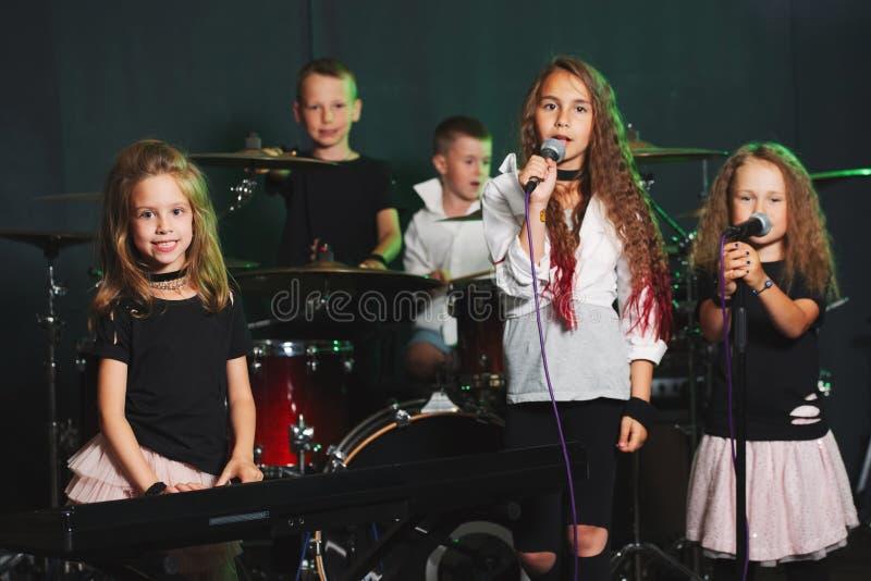 Gelukkige kinderen die en muziek zingen spelen stock fotografie