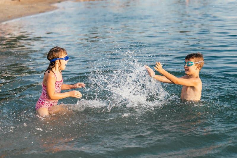 Gelukkige kinderen die in het overzees spelen stock foto