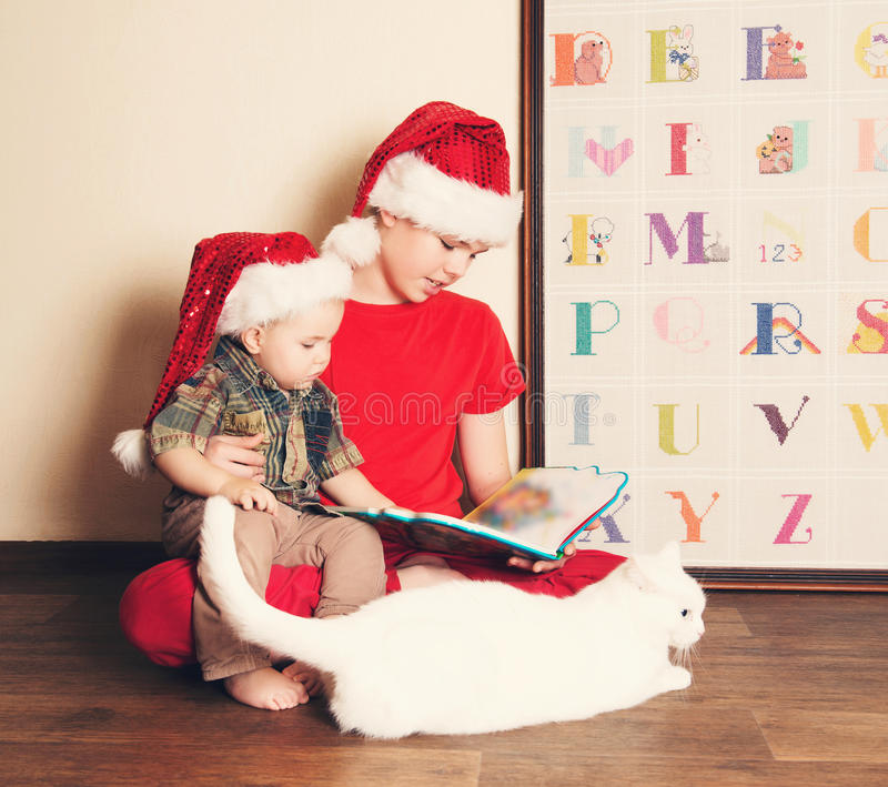 Gelukkige kinderen die in Kerstmanhoeden een Kerstmisboek lezen Grote bouillon royalty-vrije stock afbeelding