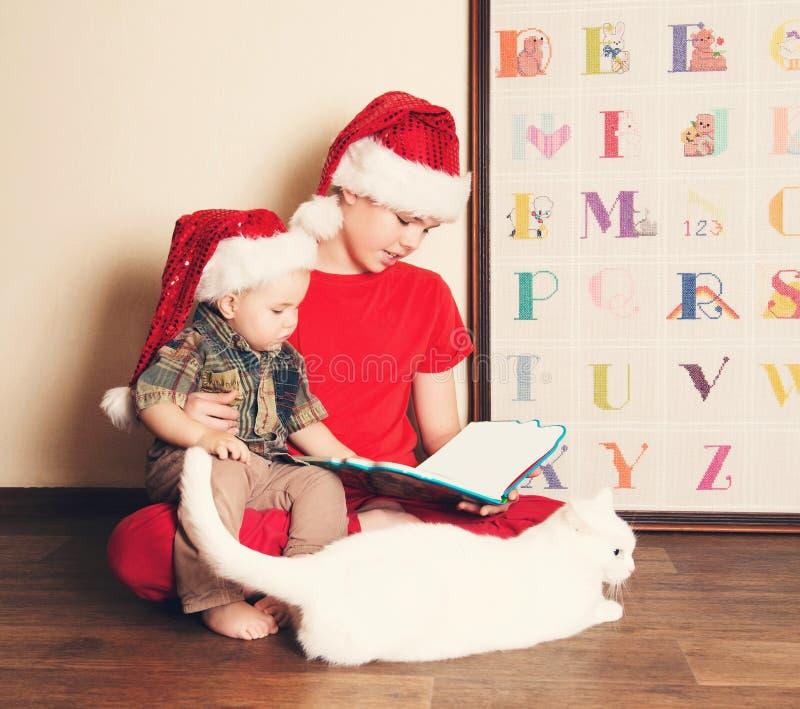 Gelukkige kinderen die in Kerstmanhoeden een Kerstmisboek lezen Grote bouillon stock afbeeldingen