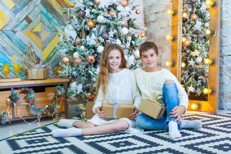 Gelukkige kinderen die Kerstmisgiften houden en op de vloer zitten stock fotografie