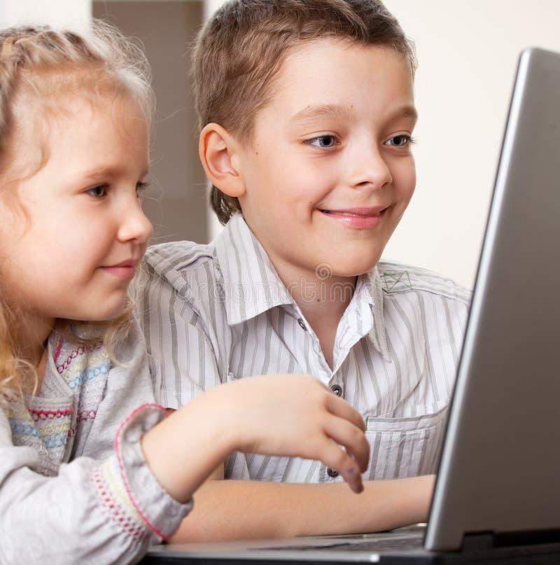 Gelukkige kinderen die laptop spelen royalty-vrije stock fotografie