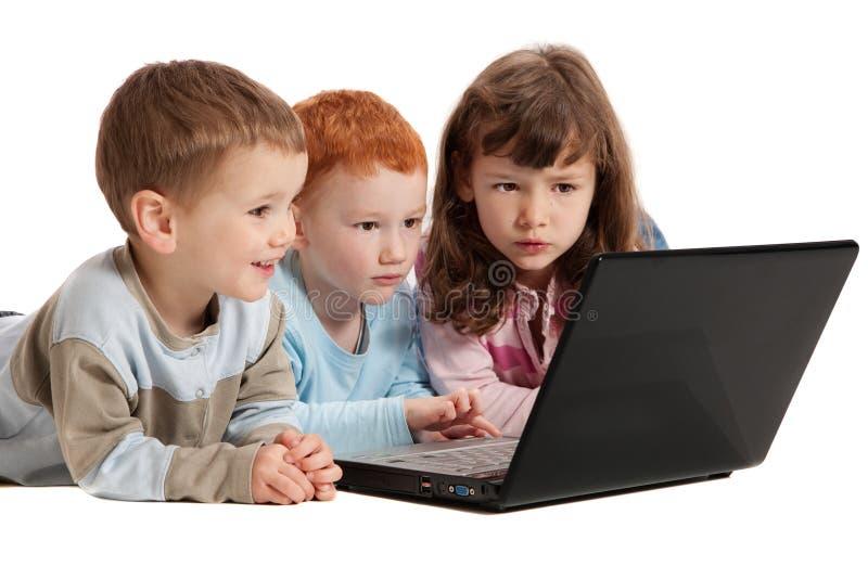 Gelukkige kinderen die op de computer van het jonge geitjesnotitieboekje leren stock foto's