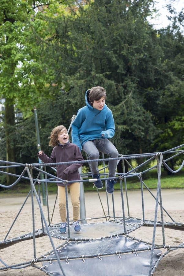 Gelukkige kinderen die op een trampoline of een elastisch bed springen stock afbeelding