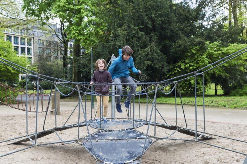 Gelukkige kinderen die op een trampoline of een elastisch bed springen royalty-vrije stock foto's