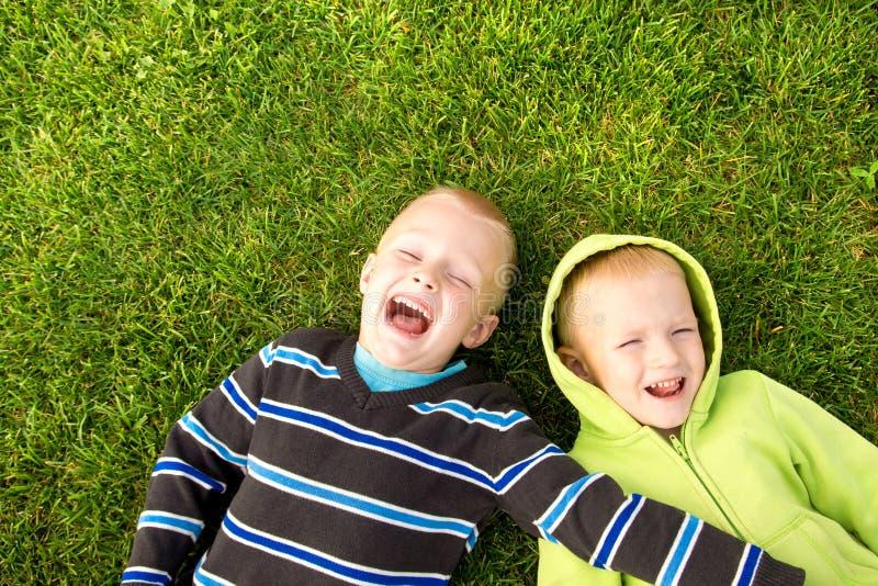 Gelukkige kinderen die op groen gras liggen stock foto's