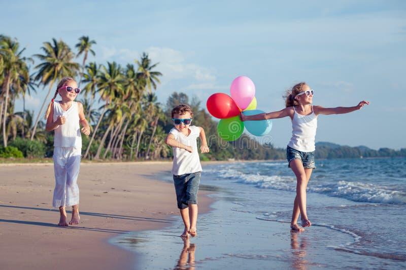 Gelukkige kinderen die op het strand in de dagtijd spelen royalty-vrije stock foto