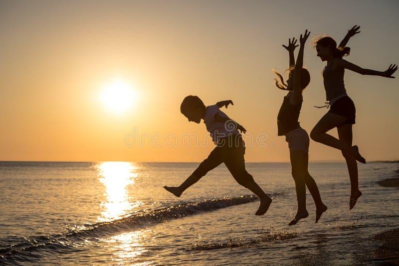 Gelukkige kinderen die op het strand in de zonsondergangtijd spelen stock afbeelding