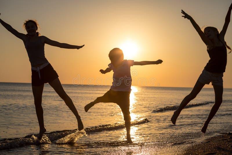 Gelukkige kinderen die op het strand in de zonsondergangtijd spelen stock afbeeldingen