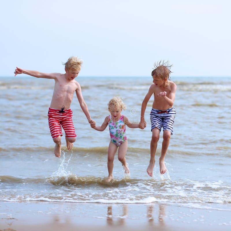 Gelukkige kinderen die op het strand spelen royalty-vrije stock fotografie