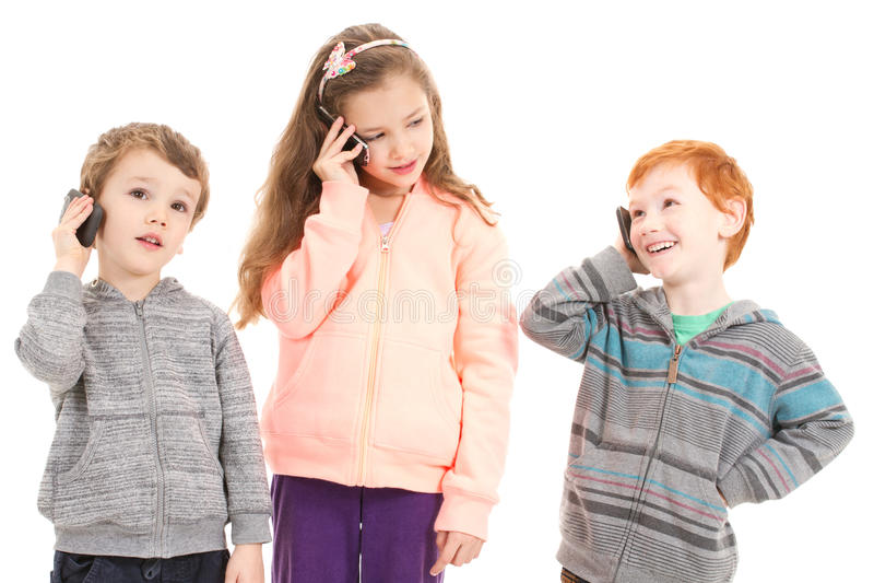 Gelukkige kinderen die op mobiele telefoons spreken royalty-vrije stock afbeeldingen
