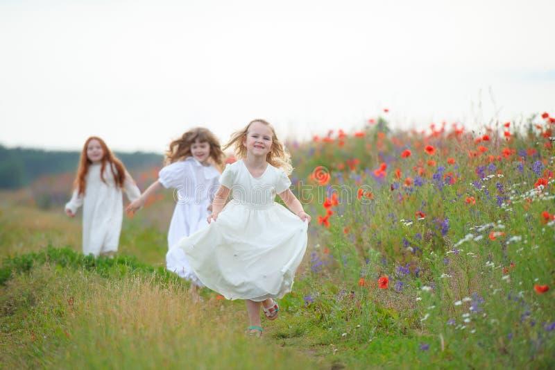 Gelukkige kinderen die in openlucht spelen Drie het jonge meisjes lopen royalty-vrije stock fotografie