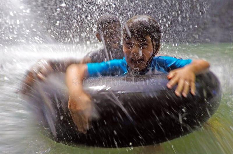 Gelukkige kinderen die pret hebben onder een waterval royalty-vrije stock afbeeldingen