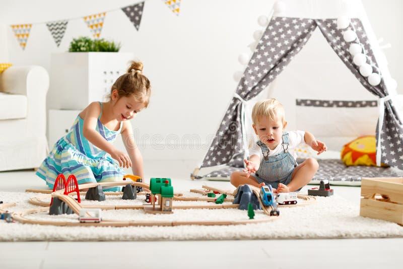 Gelukkige kinderen die in speelgoed thuis in speelkamer spelen royalty-vrije stock foto