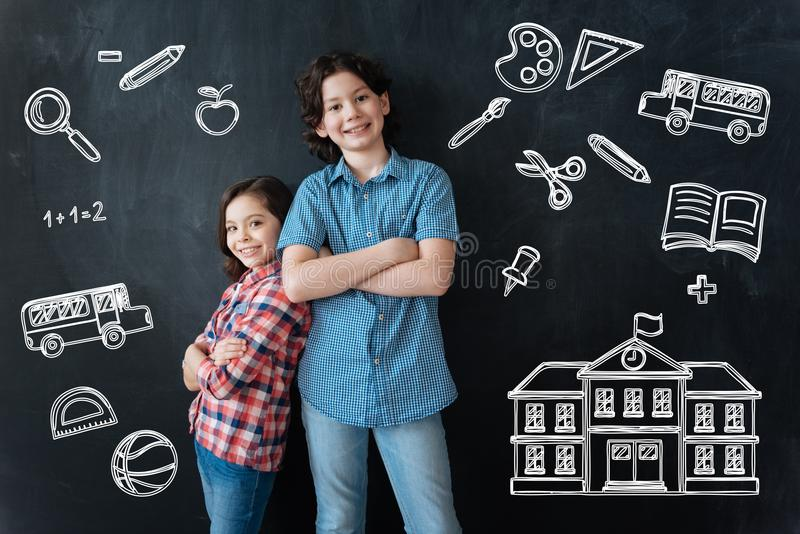 Gelukkige kinderen die zich met hun gekruiste wapens bevinden en op school wachten stock foto
