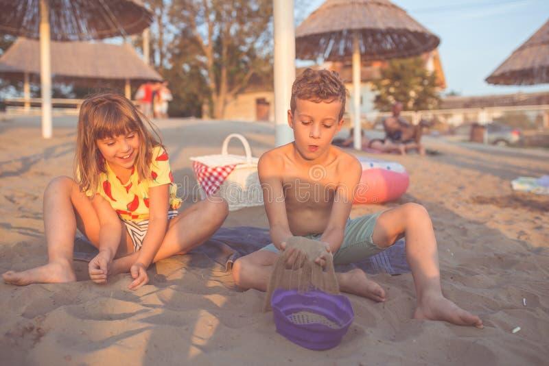 Gelukkige kinderen en het spelen met zand op het strand royalty-vrije stock afbeeldingen