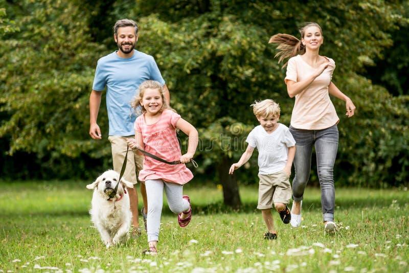 Gelukkige kinderen en ouders met hond stock afbeelding
