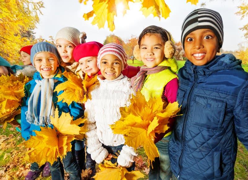 Gelukkige kinderen met bossen van gele esdoornbladeren stock foto's