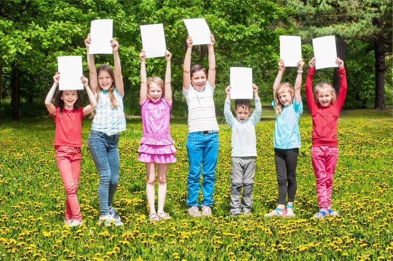 Gelukkige kinderen met witte banner stock fotografie