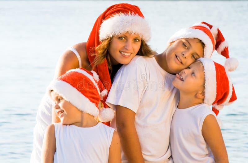 Gelukkige kinderen op het strand met Kerstmishoeden royalty-vrije stock foto