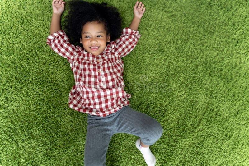 Gelukkige kinderenjonge geitjes die en op groene tapijtvloer thuis glimlachen leggen in woonkamer royalty-vrije stock foto