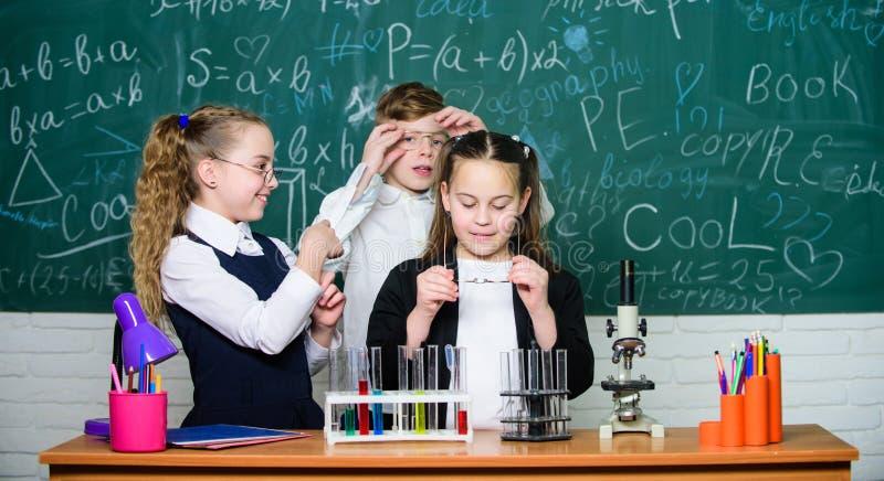 Gelukkige kinderenvriendschap groepswerk studenten die wetenschapsexperimenten met microscoop in laboratorium doen Biologiemateri stock foto