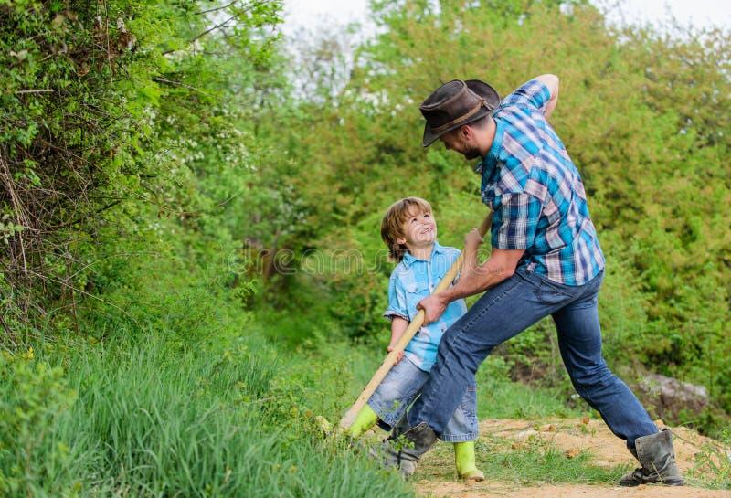 Gelukkige kinderjaren E Weinig helper in tuin Leuk kind in aard die pret met cowboy hebben stock afbeelding