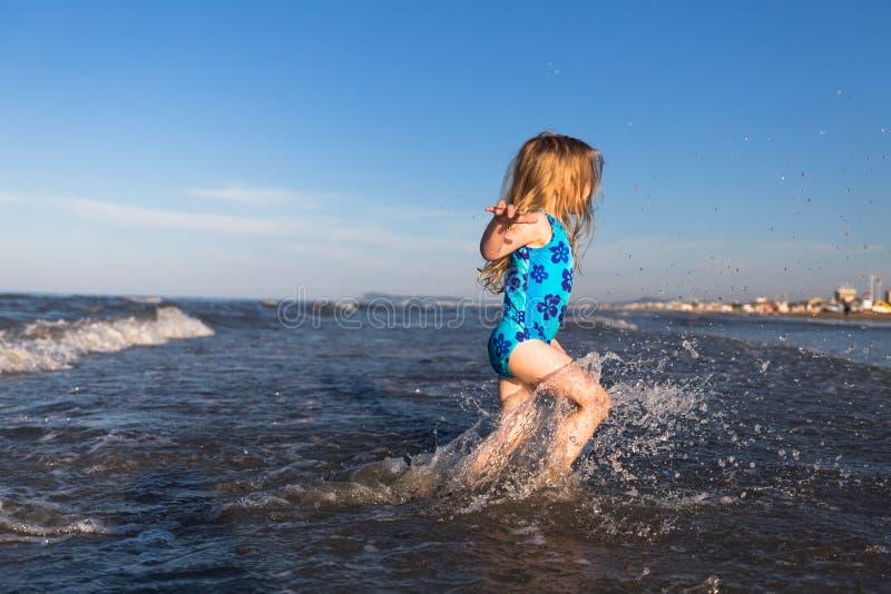 Gelukkige kinderjaren Gelukkig kind in het overzees Riminitoevlucht Italië Weinig blondemeisje die in het overzees lopen Vakantie stock foto's