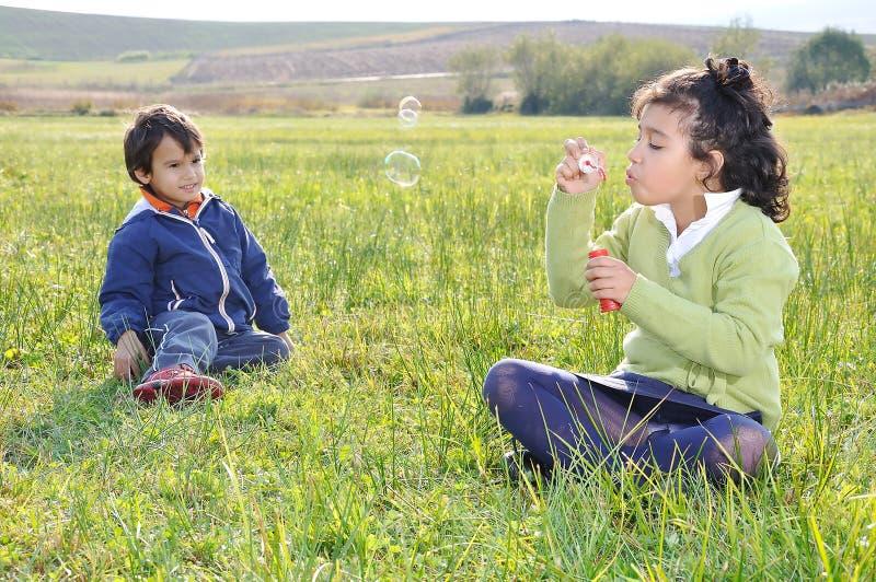 Gelukkige kinderjaren op groen stock fotografie