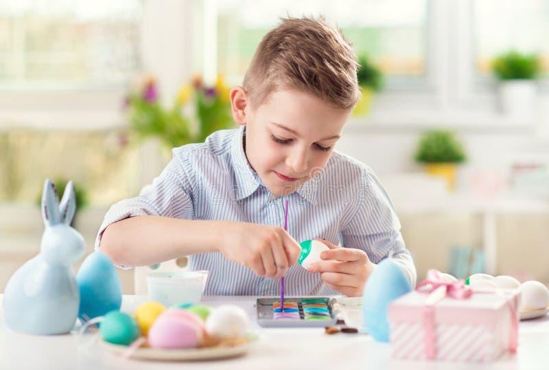 Gelukkige kindjongen die pret hebben tijdens het schilderen eieren voor Pasen in de lente stock foto's