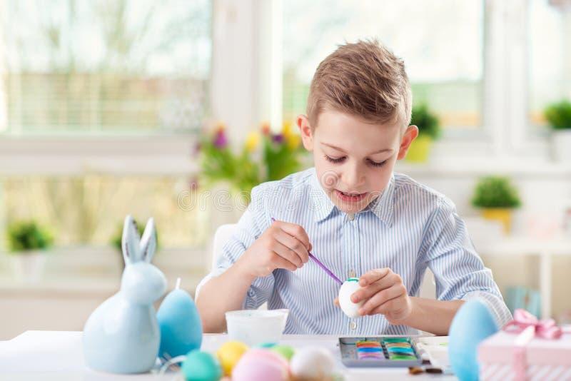 Gelukkige kindjongen die pret hebben tijdens het schilderen eieren voor Pasen in SP stock fotografie