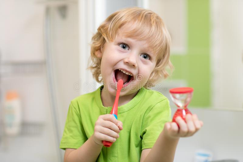 Gelukkige kindjongen het borstelen tanden dichtbij spiegel in badkamers Hij controleert het duren van het schoonmaken actie met z stock foto