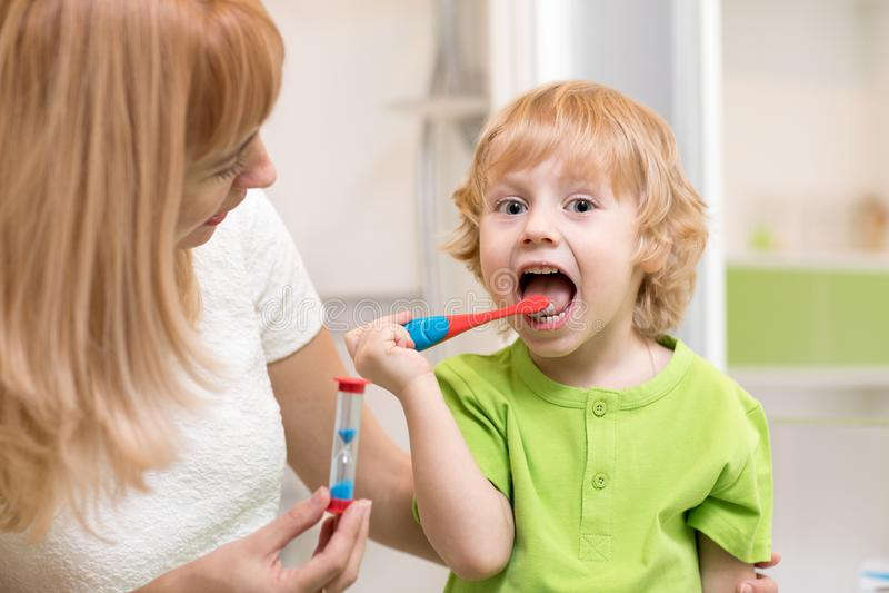 Gelukkige kindjongen het borstelen tanden dichtbij spiegel in badkamers Zijn moeder controlenauwkeurigheid en tijd van het schoon stock afbeelding
