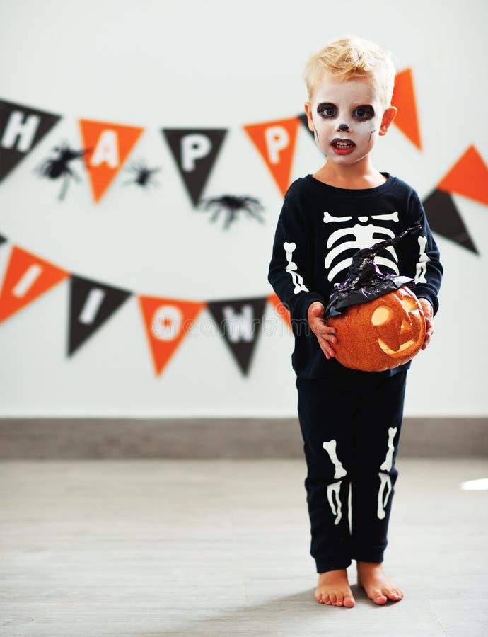 Gelukkige kindjongen in skeletkostuum aan Halloween stock foto