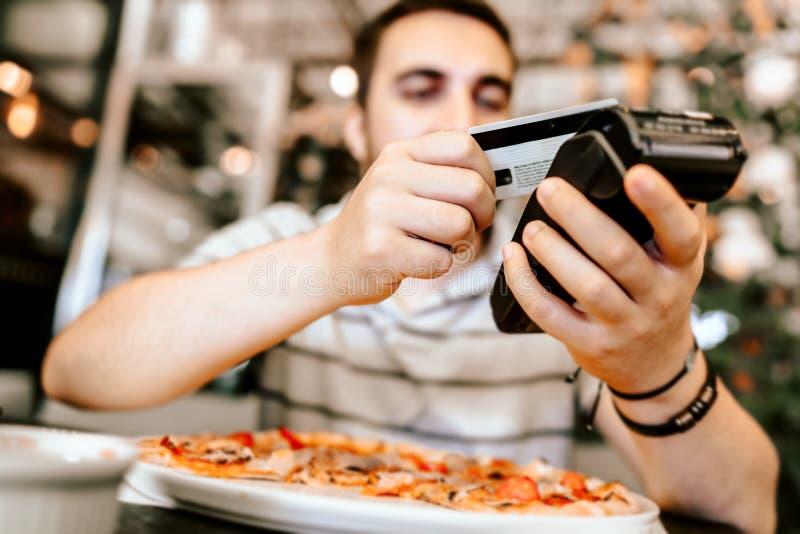 Gelukkige klant die moderne technologiebetalingswijze gebruiken die - met creditcard op draadloze terminal betalen stock foto's