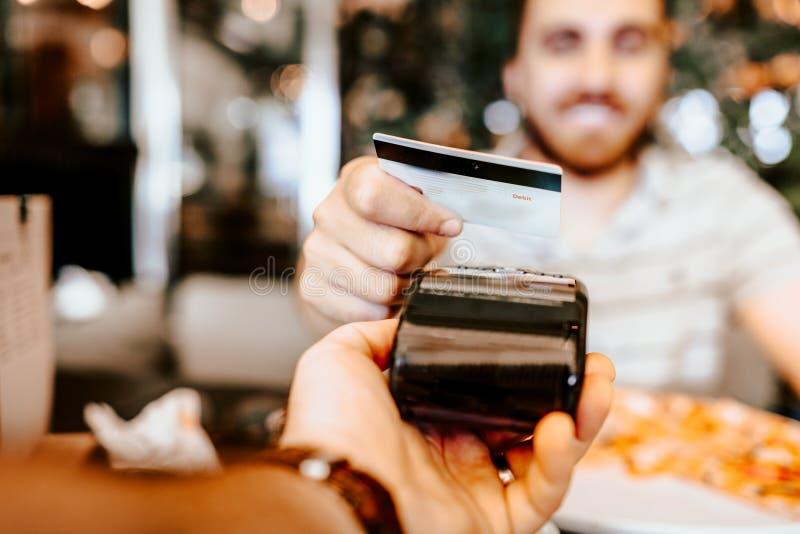 Gelukkige klant die voor lunch betalen die nieuwe, moderne technologie zonder contact met creditcard gebruiken stock fotografie