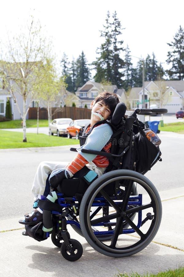 Gelukkige kleine gehandicapte jongen in rolstoel stock afbeeldingen