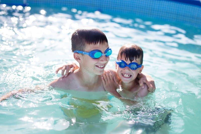 Gelukkige kleine jonge geitjes die in zwembad spelen stock afbeeldingen