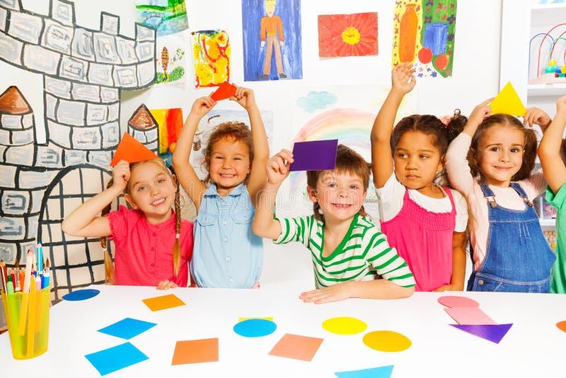 Gelukkige kleine jonge geitjes met de vormen van het kleurenkarton stock foto
