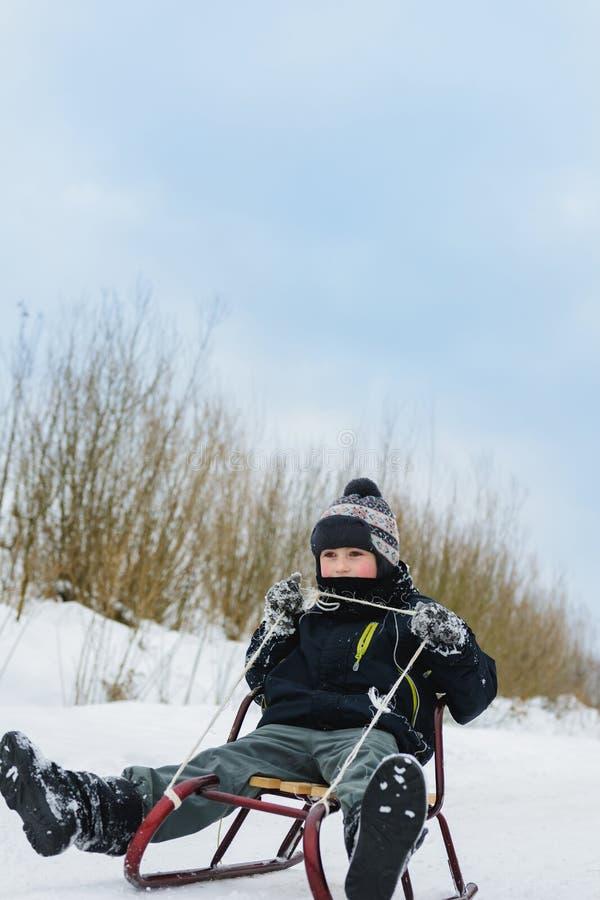 Gelukkige kleine jongen in de wintersneeuw behandelde binnenplaats stock fotografie