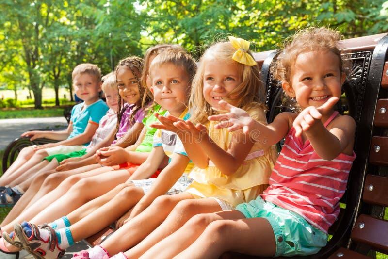 Gelukkige kleine jongens en meisjes op de bank in park royalty-vrije stock afbeelding