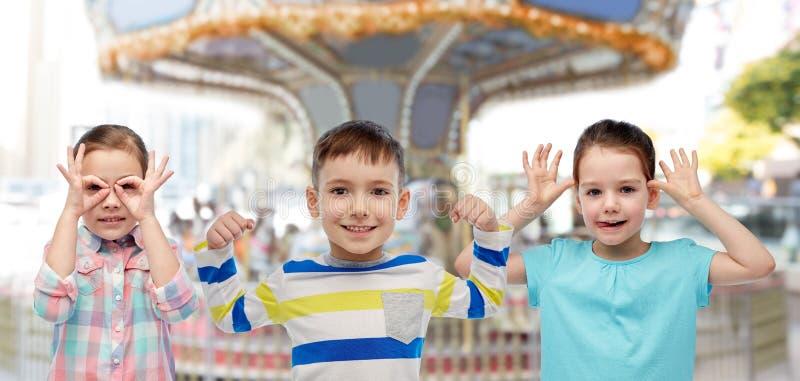 Gelukkige kleine kinderen die pret over carrousel hebben stock foto's