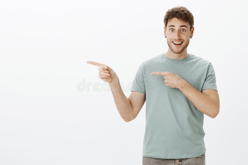 Gelukkige knappe jonge mens met links met wijsvingers richten en oorringen die, die ontzagwekkend iets tonen vreugdevol glimlache stock foto's