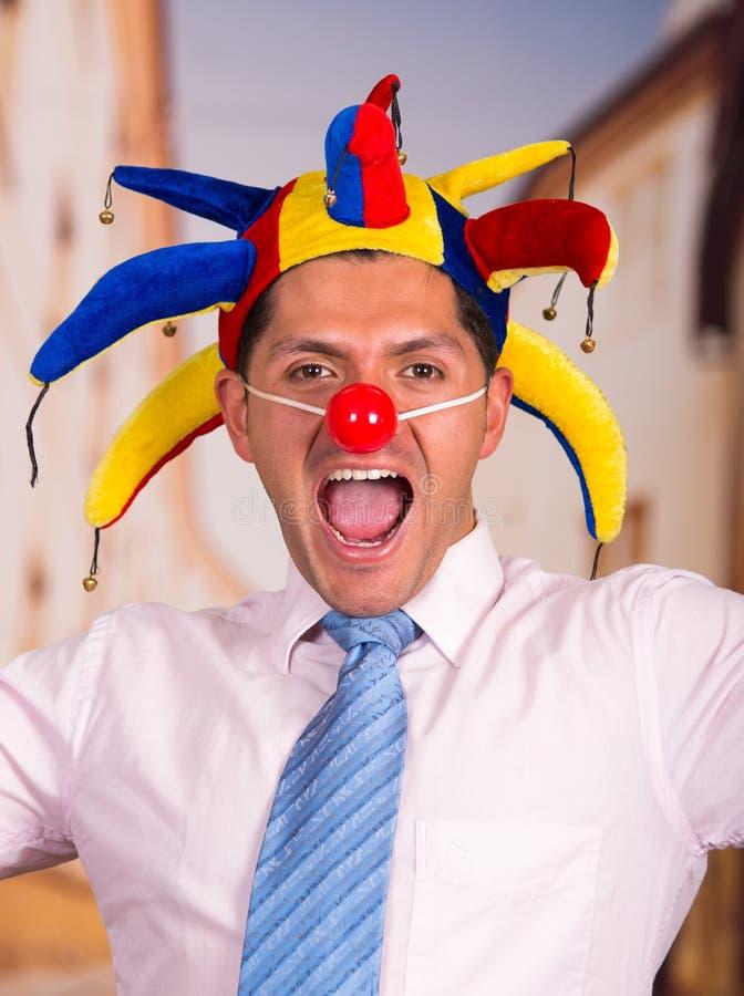 Gelukkige knappe jonge zakenman met een rode clownneus en kleurrijke harlekijnhut in zijn hoofd stock foto