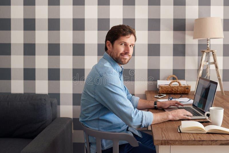Gelukkige knappe mens die van huis aan laptop werken stock afbeelding