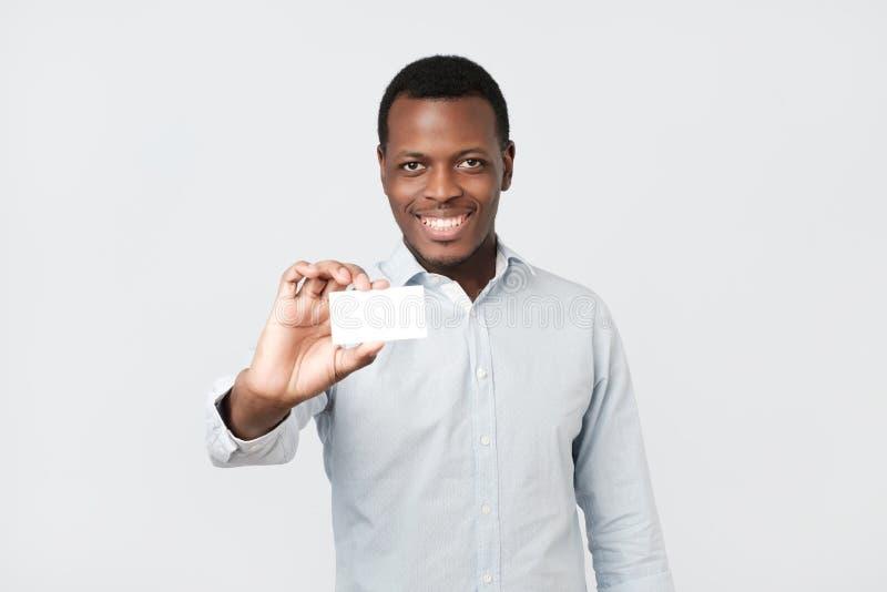 Gelukkige knappe professionele Afrikaanse Amerikaanse zakenman die naamkaart tonen aan cliënt stock afbeelding