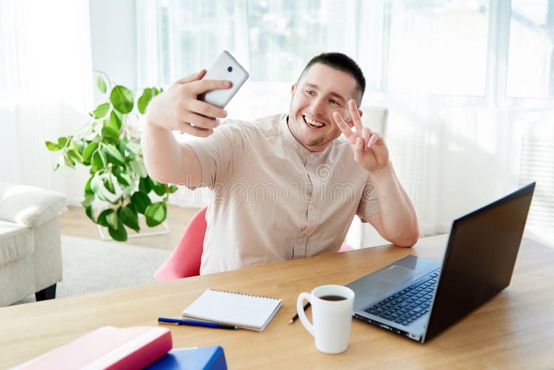 Gelukkige knappe zakenman die selfie foto op camera in modern bureau, exemplaarruimte maken stock foto's