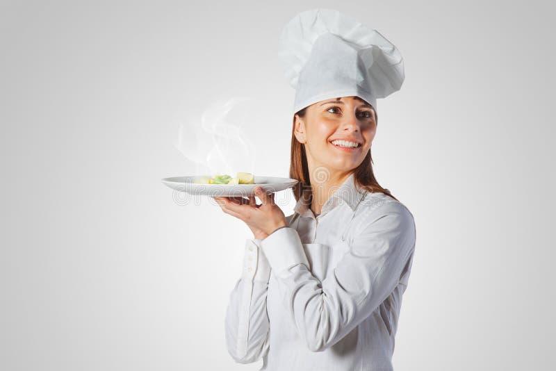 Gelukkige kokvrouw die een schotel houdt royalty-vrije stock foto's