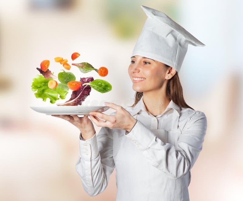 Gelukkige kokvrouw die een schotel met drijvende groenten op de keuken houdt stock foto